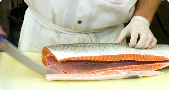 Vicente Foods seafood expert cutting salmon